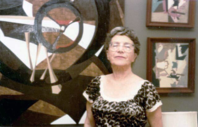 Slobodkina standing in front of paintings.